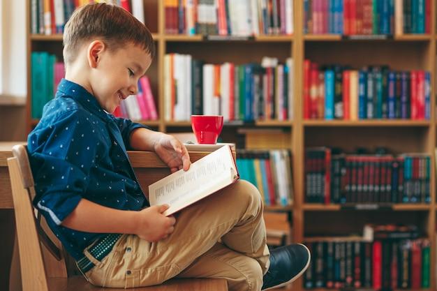 Czytanie chłopiec z filiżanką herbaty