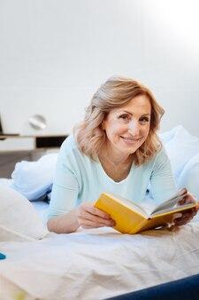 Czytanie ciekawej książki. atrakcyjna kobieta z szerokim uśmiechem niosąca żółtą książkę w twardej oprawie, leżąc na niedokończonym łóżku