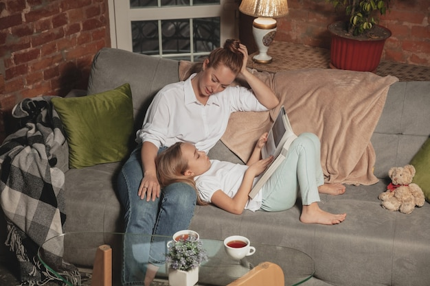 Czytanie książki. matka i córka podczas samoizolacji w domu podczas kwarantanny, rodzinne czasy przytulne i komfortowe, domowe życie. wesoła i szczęśliwa uśmiechnięta modelka. bezpieczeństwo, zapobieganie, koncepcja miłości.
