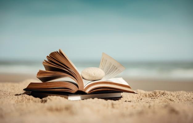 Czytanie książki odkryty w koncepcji lata. otwarta książka na piasku plaży w słoneczny dzień
