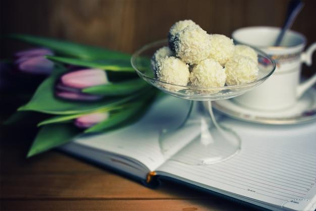 Czytanie książki z kwiatkiem herbaty i słodyczami