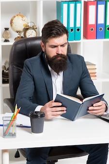 Czytanie księgi biznesowej autorytetu. człowiek brodaty hipster szef siedzieć fotel wnętrz biurowych czytać książki. szef w miejscu pracy. facet formalna odzież w stylu korporacyjnym. literatura biznesowa. szef czytał książkę.