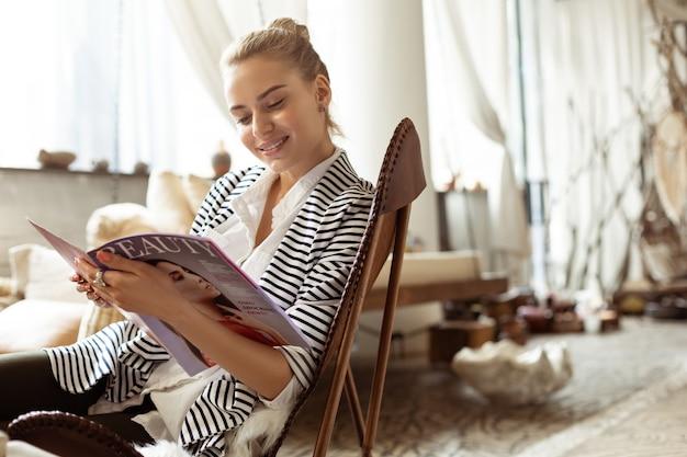 Czytanie magazynów kosmetycznych. rozpromieniona ładna kobieta czekająca na sesję w salonie i obserwująca strony magazynu