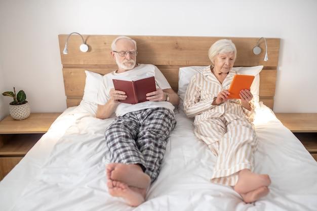 Czytanie. małżeństwo w wieku leżąc w łóżku i czytając