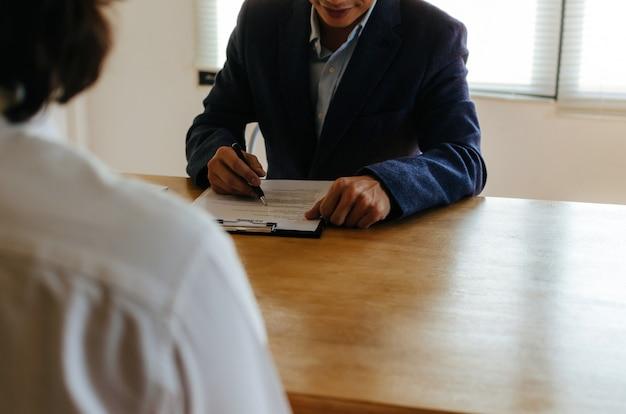 Czytanie menedżera hr firmy z młodym mężczyzną podczas rozmowy kwalifikacyjnej i wyjaśnianie o swoim profilu, siedząc w pokoju konferencyjnym w biurze, zasoby ludzkie, rozmowa kwalifikacyjna o pracy, koncepcja zatrudnienia