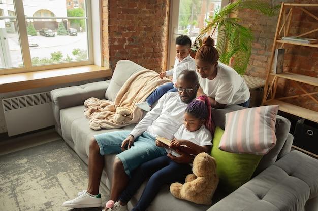 Czytanie młoda i wesoła afrykańska rodzina podczas izolacji kwarantanny spędzającej czas