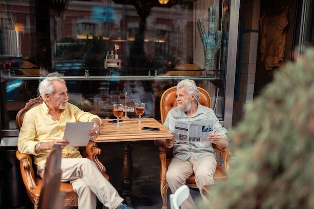 Czytanie porannych wiadomości. emerytowani mężczyźni pijący whisky i czytający poranne wiadomości siedząc na zewnątrz