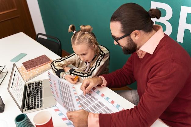 Czytanie śliczna jasnowłosa dziewczyna nosząca bransoletki na dłoni czytająca nowe słowa