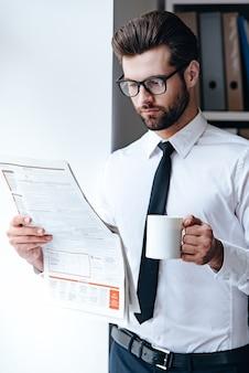 Czytanie świeżej gazety. zamyślony młody biznesmen w okularach czyta gazetę i trzyma filiżankę kawy stojąc w biurze