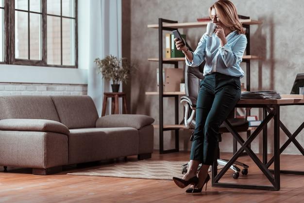 Czytanie wiadomości. piękna bizneswoman w butach na wysokim obcasie, czytająca wiadomość na telefonie i pijąca herbatę
