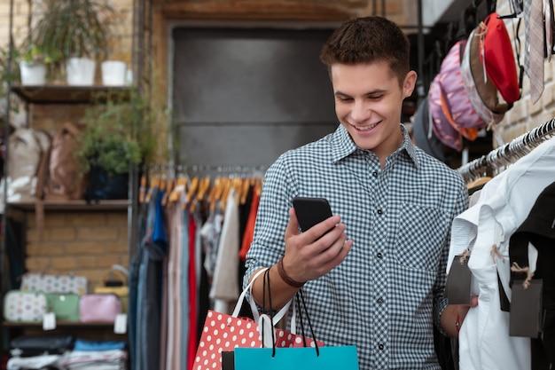 Czytanie wiadomości. pozytywny przyjazny młody człowiek stojący w sklepie z ubraniami i uśmiechnięty podczas czytania wiadomości w swoim smartfonie