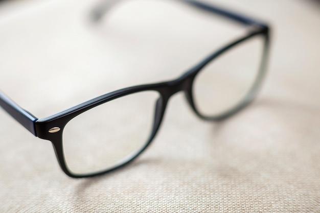 Czytelniczy widowiska, modni eyeglasses odizolowywający na zamazanym biel kopii interliniują tło.