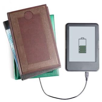 Czytnik e-booków i książka połączone kablem. białe tło.