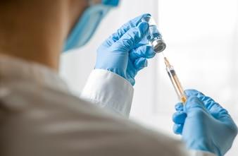 Dłoń trzymająca strzykawkę i szczepionki.