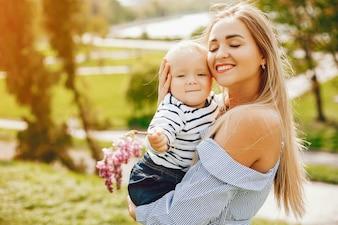 Długowłosa mama w niebieskiej sukience stojącej w słonecznym parku i trzymająca swoje dziecko