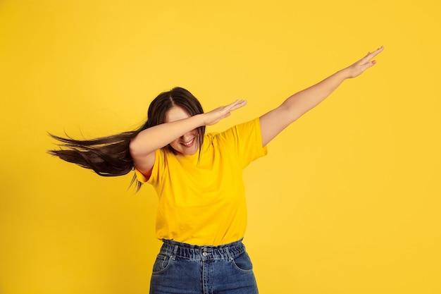Dabbing. kaukaski portret kobiety na białym tle na żółtym tle studio. piękna modelka brunetka w stylu casual. pojęcie ludzkich emocji, wyraz twarzy, sprzedaż, reklama, miejsce.
