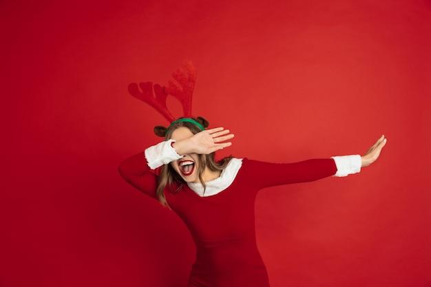 Dabbing, zimnica. koncepcja boże narodzenie, nowy rok, nastrój zimowy, święta. piękna kaukaska kobieta z długimi włosami jak renifer świętego mikołaja łapiący pudełko.