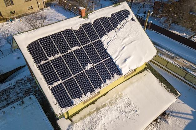 Dach domu pokryty panelami słonecznymi zimą ze śniegiem na górze. koncepcja efektywności energetycznej i konserwacji.