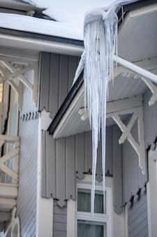 Dach drewnianego budynku pokryty ostrymi soplami. ostry sopel lodu zwisający z rynny