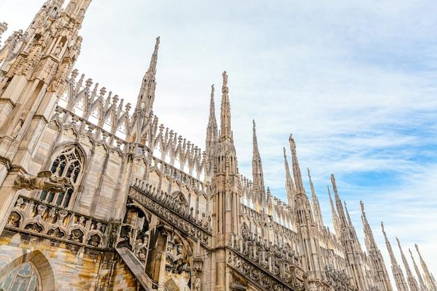 Dach katedry w mediolanie duomo di milano z gotyckimi iglicami i posągami z białego marmuru.