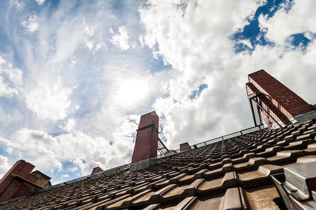 Dach kryty dachówką z ciemnopomarańczowych cegieł i żółtych kominów na tle błękitnego nieba z białymi chmurami