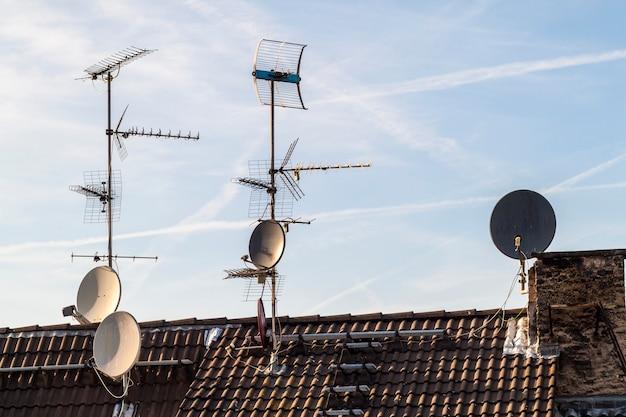 Dach starego budynku z wieloma różnego rodzaju antenami telekomunikacyjnymi