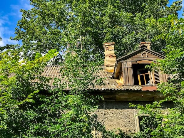 Dach zrujnowanego domu z desek szalunkowych z oknem strychowym i zielenią wokół domu