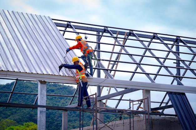 Dacharza pracownik w ochronnym jednolitym odzieży i rękawiczkach, używa pneumatycznego lub pneumatycznego pistoletu do gwoździ i instaluje gont asfaltowy na szczycie nowego dachu, koncepcja budynku mieszkalnego w budowie.