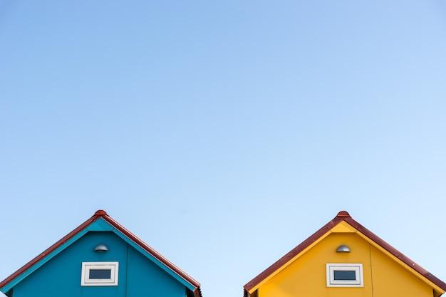 Dachy małych domów w kolorze niebieskim i żółtym z copyspace na niebie