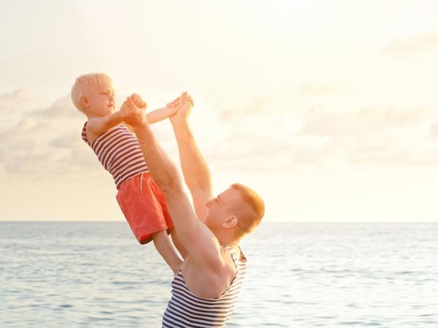 Dade trzyma syna w rozpostartych rękach na wybrzeżu. widok z tyłu