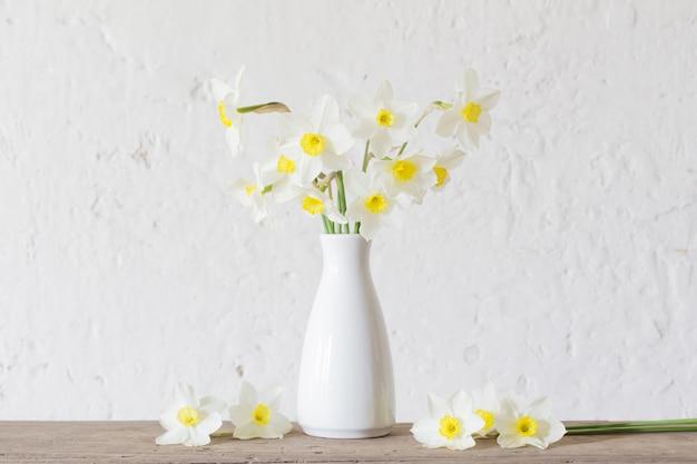 Daffodils w białej wazie na białym tle