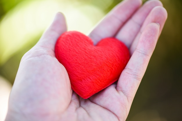 Daj love man trzymając małe czerwone serce w dłoniach dla miłości walentynki dary pomoc daj miłości ciepło dbać
