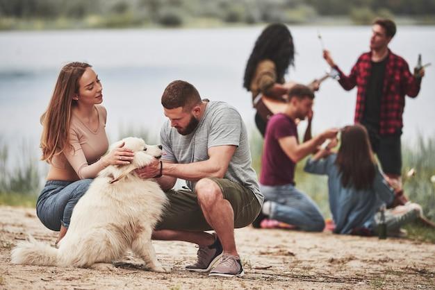 Daj mi na siebie spojrzeć. grupa ludzi ma piknik na plaży. przyjaciele bawią się w weekendy.
