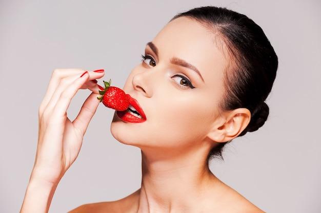 Daj się skusić! piękna młoda półnagi kobieta trzyma truskawkę w dłoni, stojąc na szarym tle
