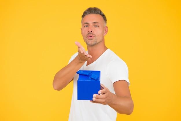 Dając całowanie dłoni. seksowny mężczyzna dać prezent urodzinowy żółte tło. obchody rocznicy urodzin. zakupy na prezent urodzinowy. zamień czyjeś urodziny w dzień pełen niesamowitości.