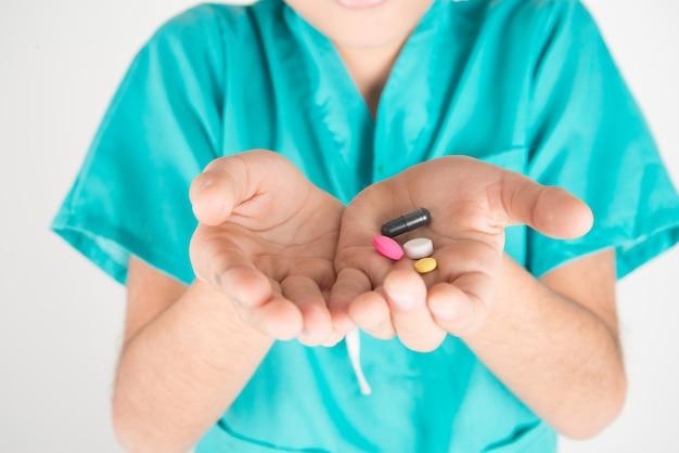 Dając dzieciom lekarstwa, chłopiec próbuje przełknąć lekarstwa na pigułki