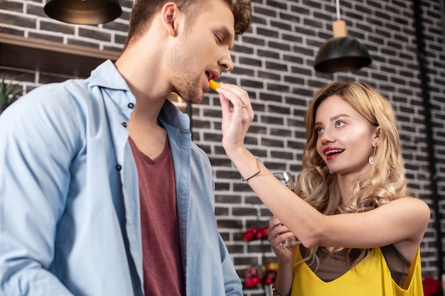 Dając pieprz. kochająca kręcona żona nosząca ładną biżuterię dająca kawałek pieprzu swojemu przystojnemu mężczyźnie