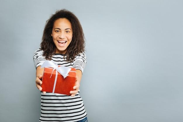 Daję ci to. zachwycona dziewczyna, trzymając uśmiech na twarzy i wyciągając ramiona z pudełkiem, patrząc prosto w kamerę