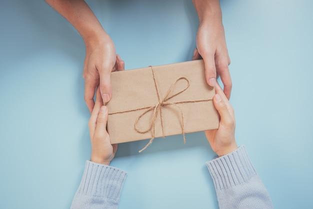 Daje prezent prezenty świąteczne i noworoczne układane na niebieskim tle.