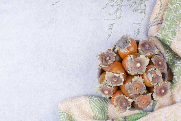 Daktylowe śliwki w drewnianym talerzu na szarym tle