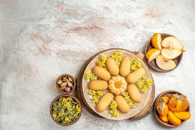 Dalekie ujęcie talerza ciastek na drewnianym talerzu i misek z owocami i suchymi kwiatami wokół niego