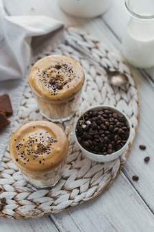 Dalgona bita kawa, rozpuszczalna, śmietankowa, mrożona. koktajl z kawą, mlekiem i kostkami lodu na lekkiej makiecie. modny napój z miejscem na tekst.