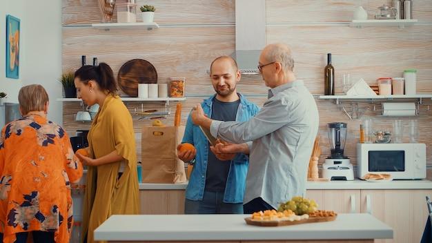 Dalsza rodzina wkładająca artykuły spożywcze do lodówki. młoda para przychodząca z zakupów przynosząca papierową torbę z zakupami, świeżą żywność z supermarketu w domu rodziców, aby przygotować rodzinny obiad