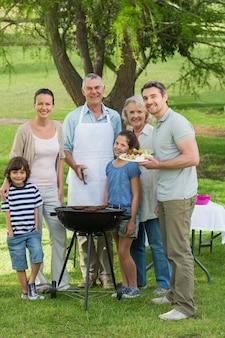 Dalszej rodziny stoi na grilla w parku