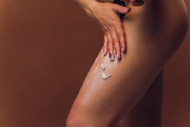 Dama dłoń na kremie do smarowania nóg pokazujący dobry wynik w bladoróżowym staniku na białym tle.