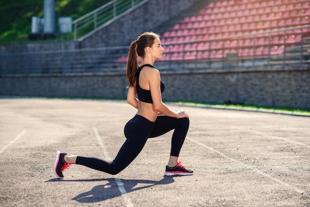 Dama fitness robi rutyny na stadionie przed treningiem, rozciąganie mięśni ciała