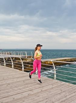 Dama fitness w odzieży sportowej działa na plaży.