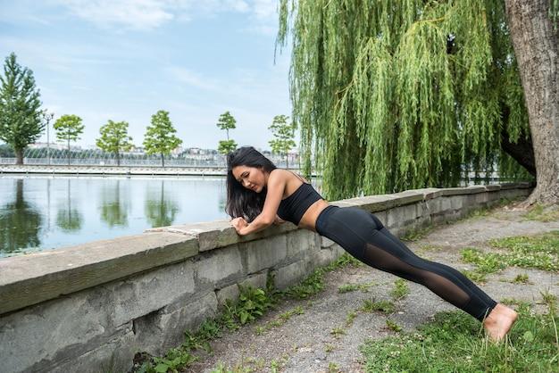 Dama fitness w odzieży sportowej robi poranne ćwiczenia rozciągające w pobliżu jeziora