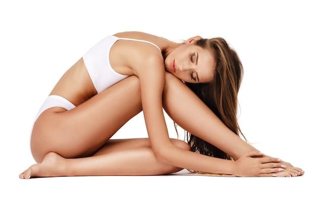 Dama fitness z pięknym ciałem na białym tle