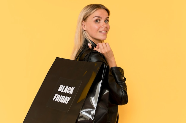 Dama mody sideview ubrana w czarne ubrania, trzymając czarną torbę na piątek